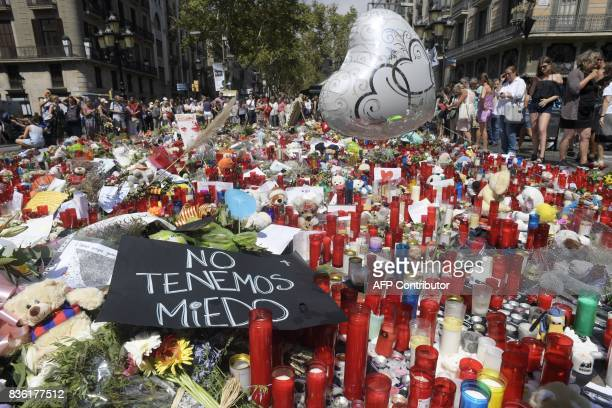 People display flowers candles balloons and many objects to pay tribute to the victims of the Barcelona and Cambrils attacks on the Rambla boulevard...