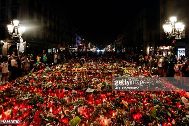 TOPSHOT People display flowers messages and candles to pay tribute to the victims of the Barcelona and Cambrils attacks on the Rambla boulevard in...