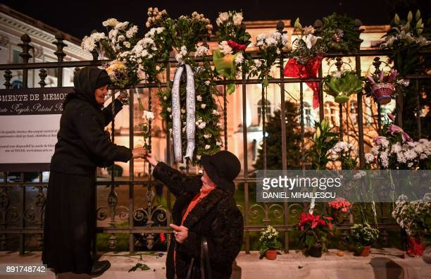 People display flowers on the grills of the former Royal Palace that houses the National Arts Museum in Bucharest before the arrival of the coffin of...