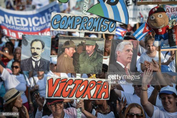 TOPSHOT People display posters of Cuban national hero Jose Marti former presidents Raul and Fidel Castro and current President Miguel DiazCanel...