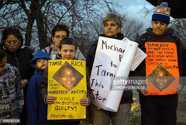 People display sigs at Cudell Commons Park in Cleveland Ohio November 24 2014 during a rally for Tamir Rice a 12yearold boy shot by police on...