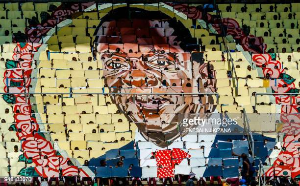 TOPSHOT People display the portrait of Zimbabwe's President Emmerson Mnangagwa during Independence Day celebrations at the National Sports Stadium on...