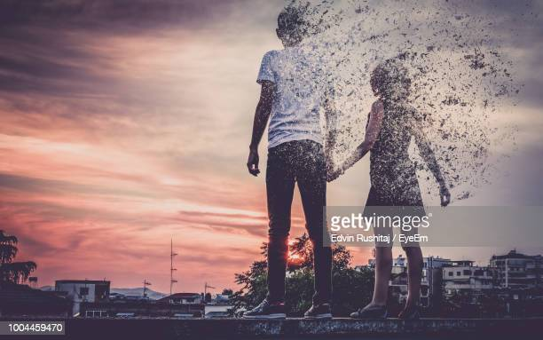 people dissolving while standing in city against sky - dissolving stock pictures, royalty-free photos & images