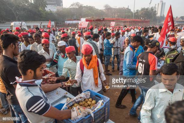 People distribute free vada pav to farmers during farmers protest march at Azad Maidan on March 12 2018 in Mumbai India Over 30000 farmers from...
