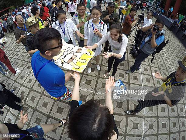 People divide a large birthday cake which a cartoon twins in rafting carved on during the 10th anniversary celebration for twins rafting race at the...