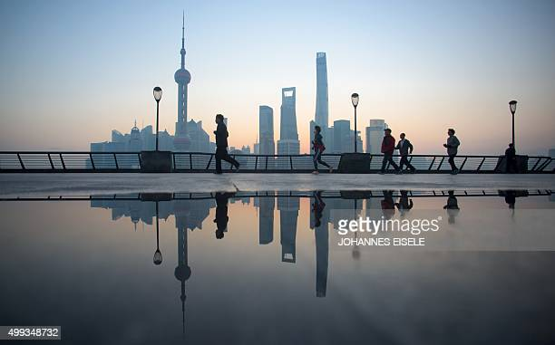 People do their morning exercises in front of the skyline of the Lujiazui Financial District in Pudong in Shanghai on December 1 2015 AFP PHOTO /...