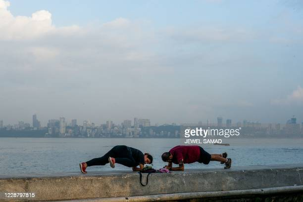 People do yoga at the Marine Drive waterfront in Mumbai on September 30, 2020.