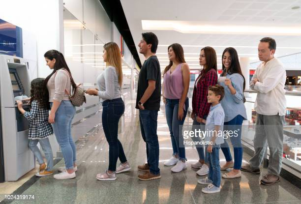 people doing a queue at the shopping mall to withdraw money from an atm - lining up stock pictures, royalty-free photos & images