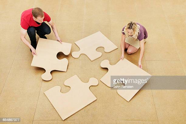 People doing puzzles with oversized props