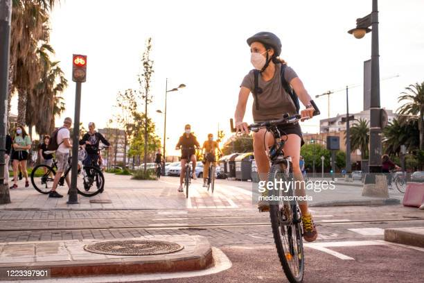 people doing sport and walking during the coronavirus pandemic on the paseo marítimo in valencia, spain - riding stock pictures, royalty-free photos & images