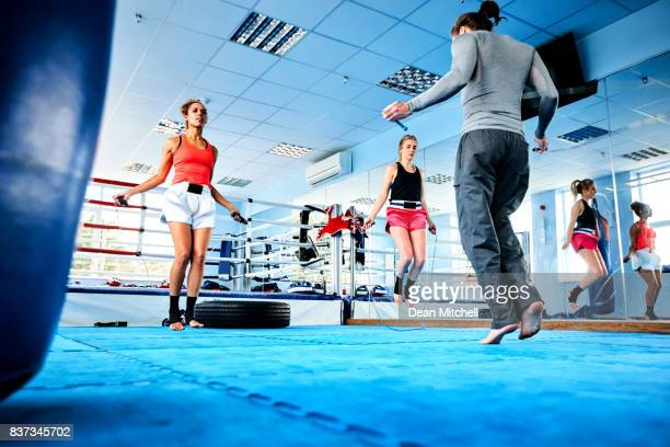 people doing warm up exercise at gym class - circuit training stock photos and pictures