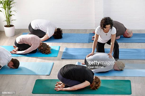 people doing yoga with instructor at health club - yoga teacher stock pictures, royalty-free photos & images