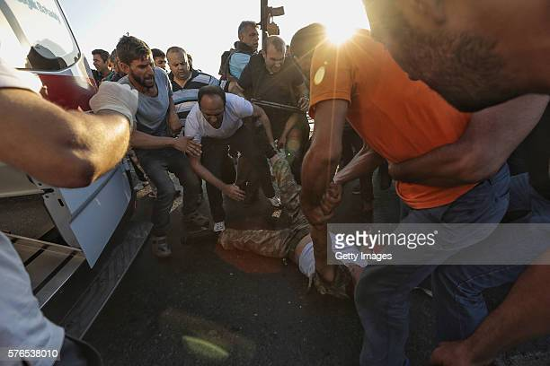 People drag a soldier after troops involved in the coup surrendered on the Bosphorus Bridge in Istanbul July 16 2016 Turkey Istanbul's bridges across...