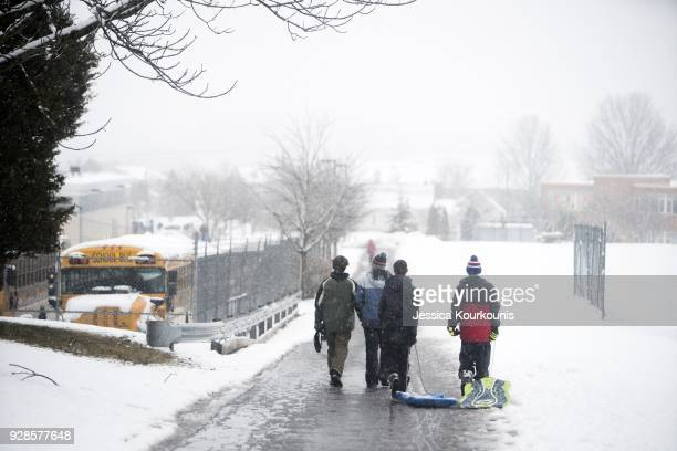 People drag and carry sleds through winter weather on March 7 2018 in Perkasie Pennsylvania This is the second nor'easter to hit the Northeast within...