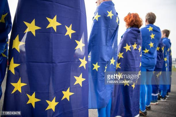 People draped in EU flags protest against the Alternative for Germany farright party as they launch their European Parliament election campaign in...