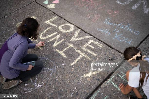 """People draw messages with chalk in an intersection that saw clashes between police and protesters just days before in the so-called """"Capitol Hill..."""
