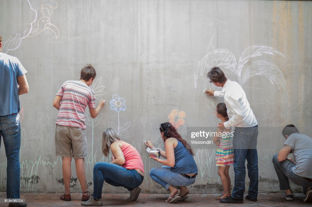 People drawing colourful pictures with chalk on a concrete wall : Stock Photo