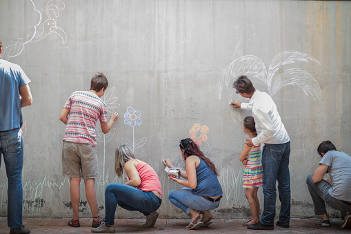 People drawing colourful pictures with chalk on a concrete wall - gettyimageskorea