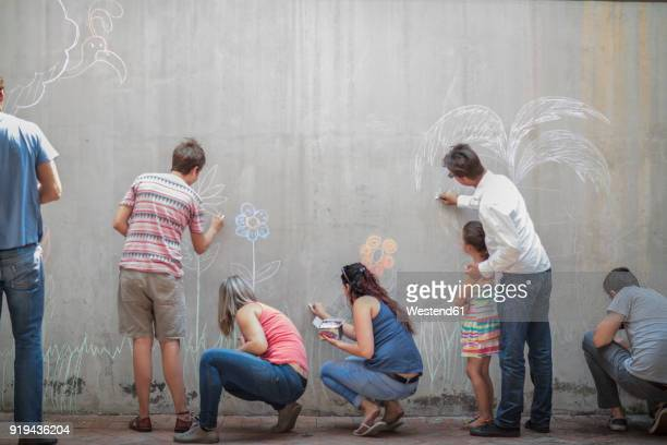 People drawing colourful pictures with chalk on a concrete wall