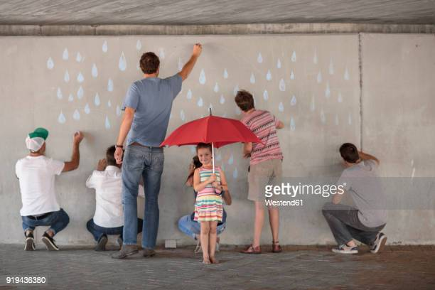 People drawing raindrops on concrete wall, little girl standing holding red umbrella
