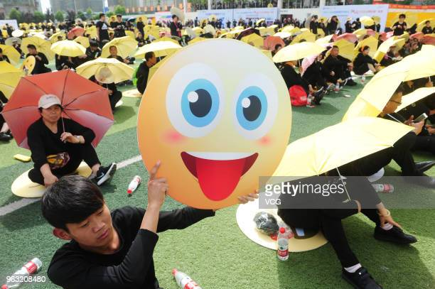 People dress as emoji faces to set an Guinness World Record on a school playground on May 27 2018 in Fuyang Anhui Province of China Guinness World...