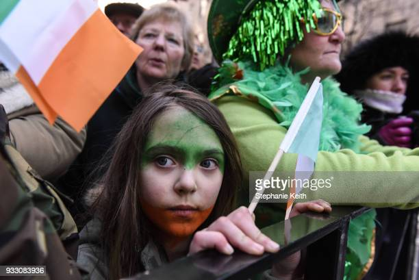 People dress in Irish colors along the sidelines of the annual St Patrick's Day parade along 5th Ave on March 17 2018 in New York City New York's...