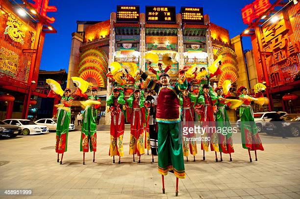 People dress in traditional Chinese style walk on stilts