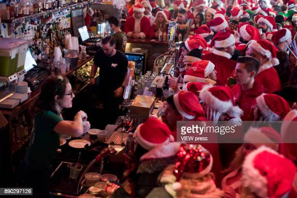 People dressed as a Santas drink at a bar in Manhattan during the annual SantaCon pub crawl on December 9 2017 in New York City Hundreds of revelers...