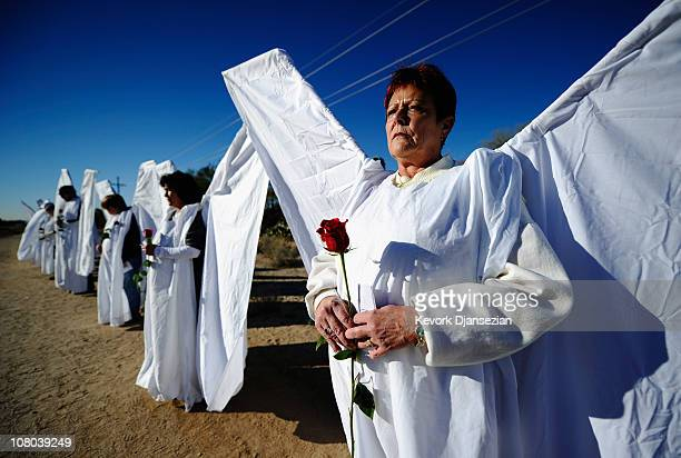 People dressed as angels hold red roses and stand across the street from St Elizabeth Ann Seton church where the funeral service for US District...