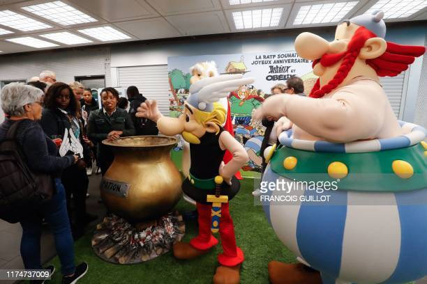 People dressed as Asterix and Obelix gesture as people gather to commemorate the 60th anniversary of France's famous comic characters Asterix and...