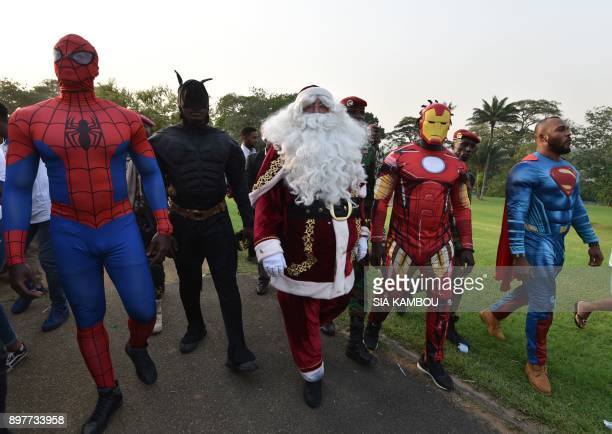 People dressed as Batman Santa Claus Iron Man and Superman walk at the presidential palace in Abidjan on December 23 during a Christmas event...