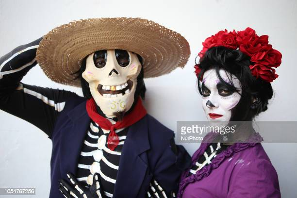 people dressed as Catrin and Catrina pose for photo in festival celebrating the day of Los Muertos in Sao Paulo on October 28 2018