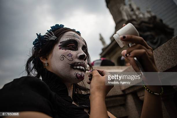 People dressed as Catrina take part in the Catrinas procession at Reforma Avenue Mexico City Mexico on October 23 2016 The Catrina is a popular...