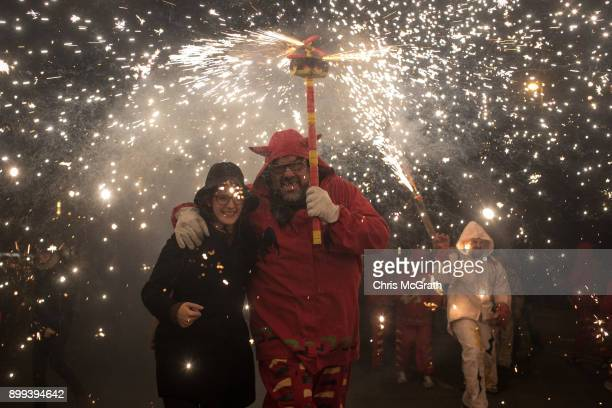 People dressed as devils dance in the street under fire torches during the festival Nit de Llufes on December 28 2017 in Barcelona Spain People dance...