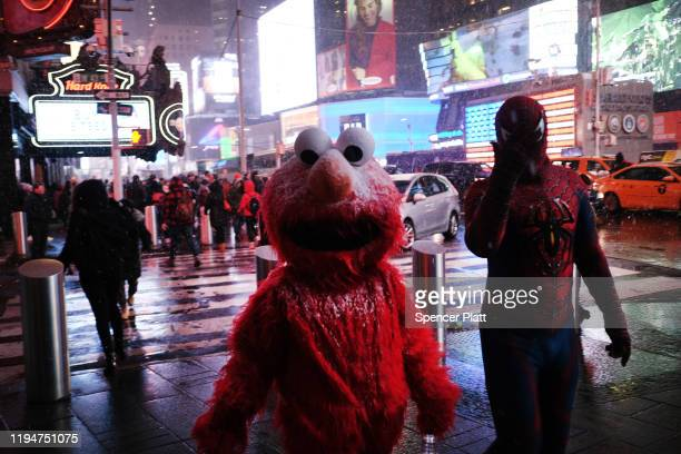 People dressed as Elmo and Spiderman walk through a snow squall in midtown Manhattan on December 18 2019 in New York City As the afternoon storm blew...