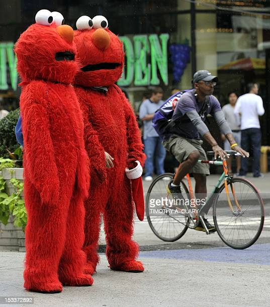 People dressed as Elmo from the television show Sesame Street wait to pose for pictures with tourists in Times Square October 4 2012 GOP Presidential...