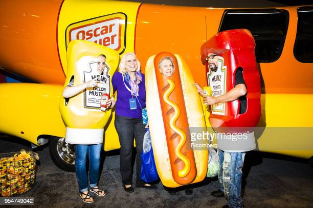 People dressed as Kraft Heinz Co Ketchup and Yellow Mustard bottles stand for a photograph with attendees in front of an Oscar Meyer Wienermobile...