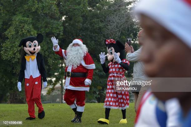 People dressed as Mickey Mouse Santa Claus and Minnie Mouse walk as they arrive at the presidential palace in Abidjan on December 22 during a...