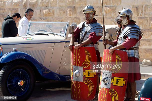 People dressed as Roman Centurions look on as classic car owners taking part in the '2011 Jordan Classic' arrive at the ancient Roman city of Jerash...