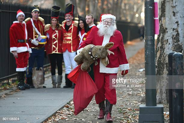 People dressed as Santa and other holiday related outfits parade around the Brooklyn section of the city during the SantaCon 2015 in New York City...