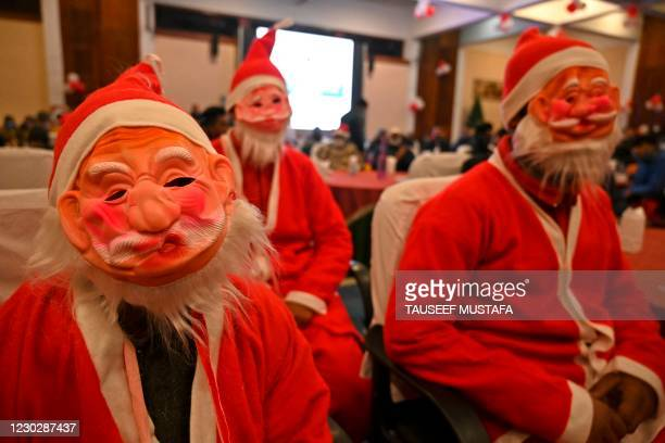 People dressed as Santa Claus attend a function organised by the Jammu and Kashmir Tourism Department on the eve of Christmas in Srinagar on December...