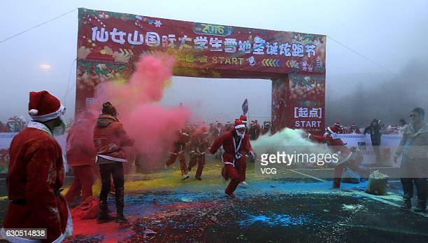 People dressed as Santa Clause compete in the color run at Xiannu Mountain on December 24 2016 in Chongqing China About 6000 students and citizens...