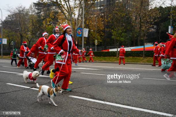 People dressed as Santa Claus running with their dogs during the annual Santa Claus Christmas race