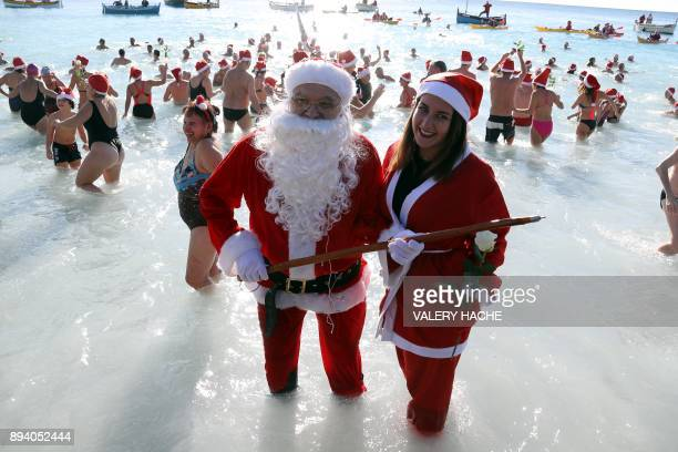 People dressed as Santa Claus take part in the traditional Christmas bath on December 17 2017 in the French riviera city of Nice / AFP PHOTO / VALERY...