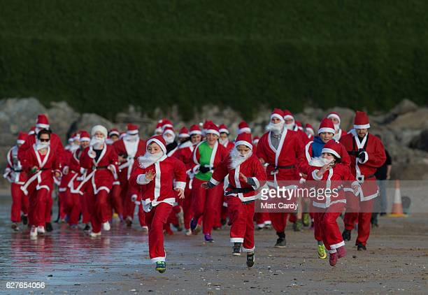 People dressed as Santa take part in the beach fun run as part of the Santa Run and Surf 2016 at Fistral Beach in Newquay on December 4 2016 in...