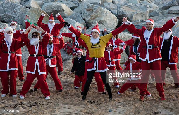 People dressed as Santa warm up prior to taking part in the beach fun run as part of the Santa Run and Surf 2016 at Fistral Beach in Newquay on...