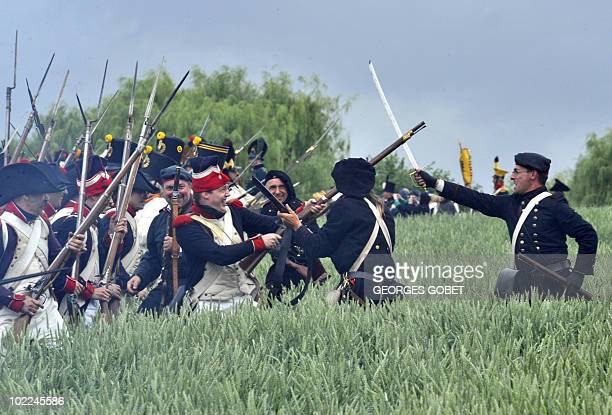 People dressed as soldiers fight during a reenactment of the 1815 Battle of Waterloo between the French army led by Napoleon and the Allied armies...