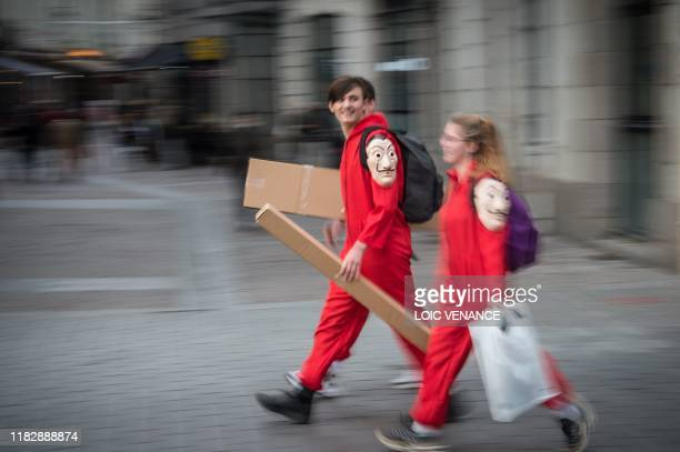 People dressed as Spanish TV show Casa de Papel characters walk in the street during a demonstration marking the first anniversary of the yellow vest...