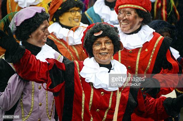 People dressed as 'Stroopwafel Petes' with striped light brown faces gesture during celebrations to welcome Sinterklaas the Dutch version of Santa...