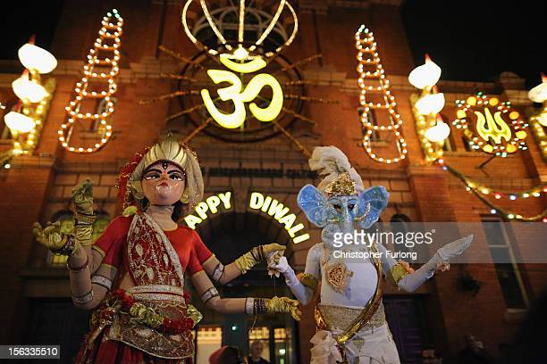 People dressed as the gods Lord Ganesha and Goddess Lakshmi walk through the streets during the Hindu festival of Diwali on November 13 2012 in...